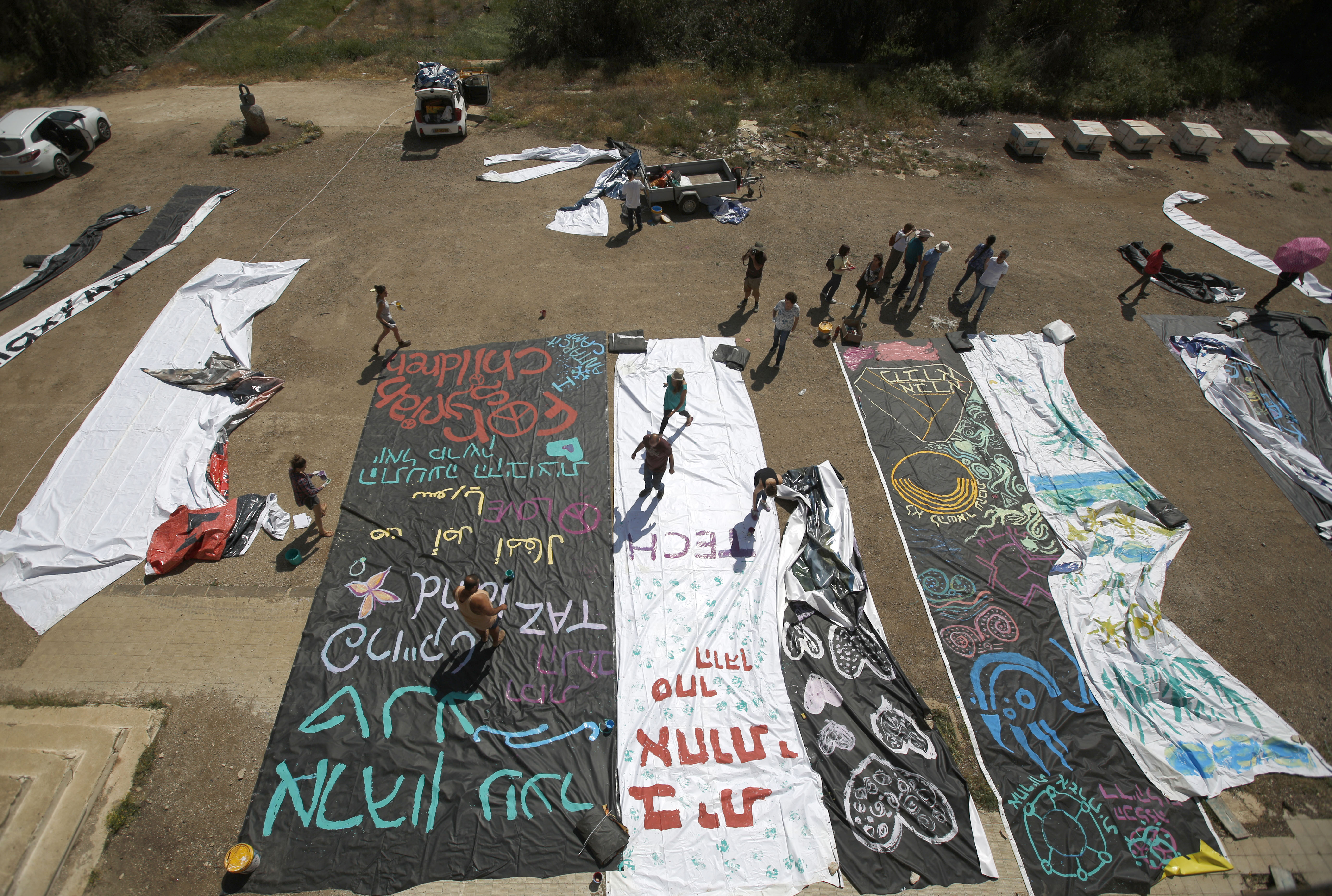 Israeli teenagers paint a huge canvas with slogans in Arabic and