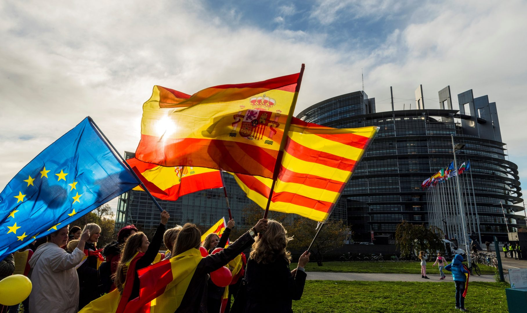 Women hold Spanish, Catalan and European flags during a